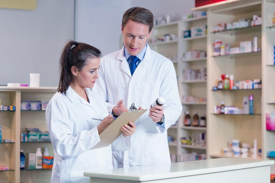 """Trainee holding a prescription while talking to the pharmacist"" stock image"