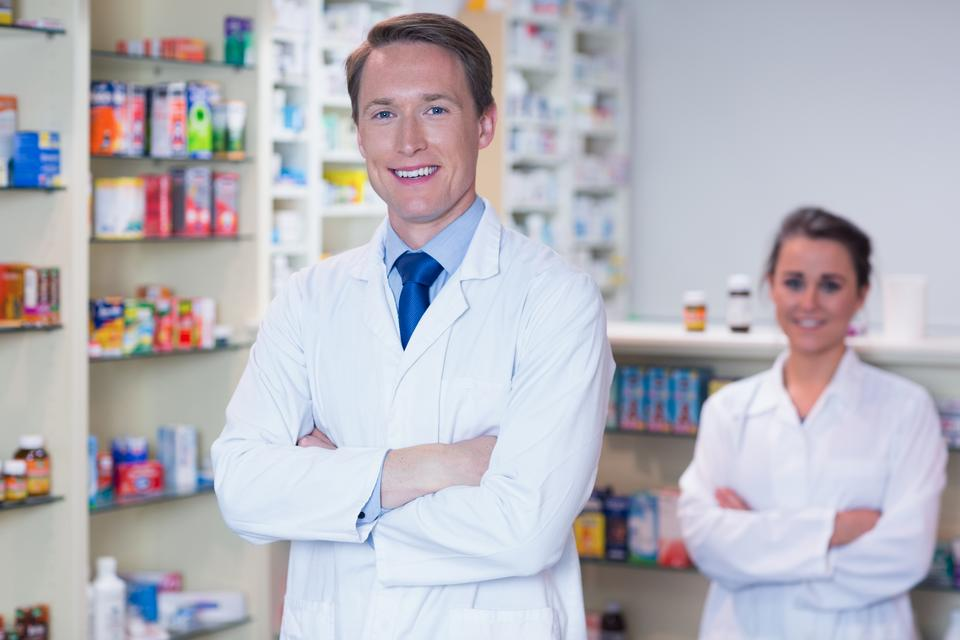 """Pharmacist with his trainee standing with arms crossed"" stock image"