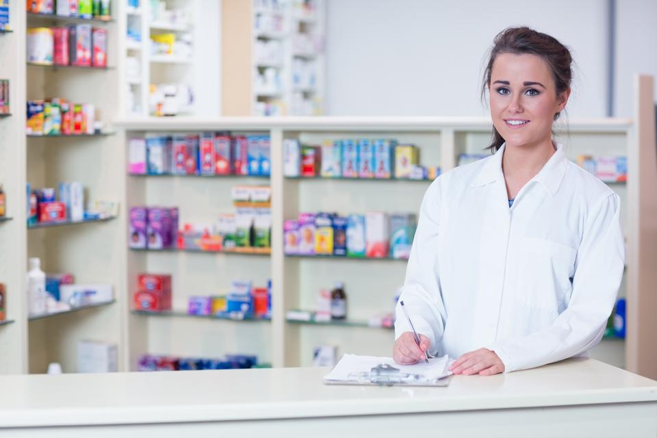 """Smiling trainee in lab coat writing a prescription"" stock image"