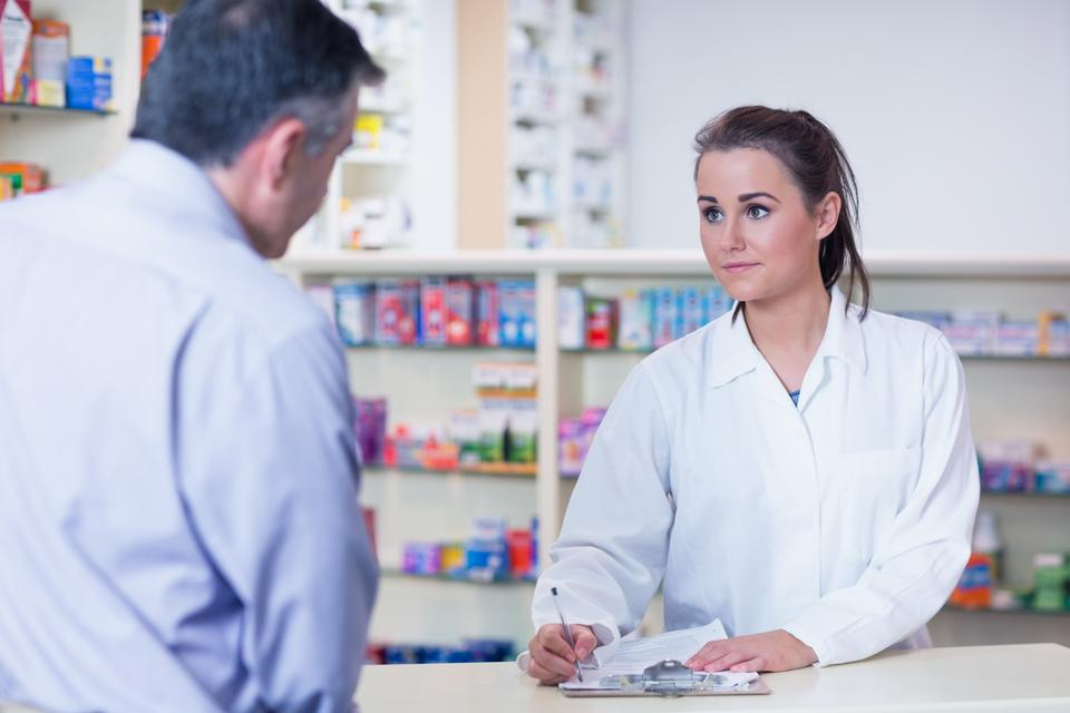 """Trainee writing prescription in front of a customer"" stock image"