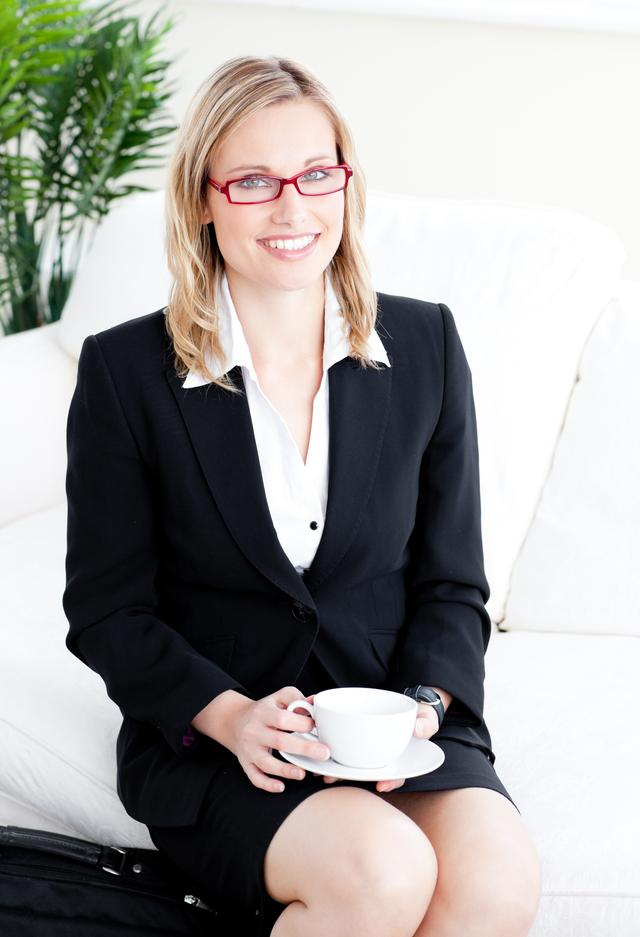 """""""Captivating businesswoman holding a cup sitting on a sofa"""" stock image"""