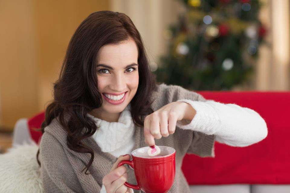 """Brunette dunking marshmallow in hot chocolate at christmas"" stock image"