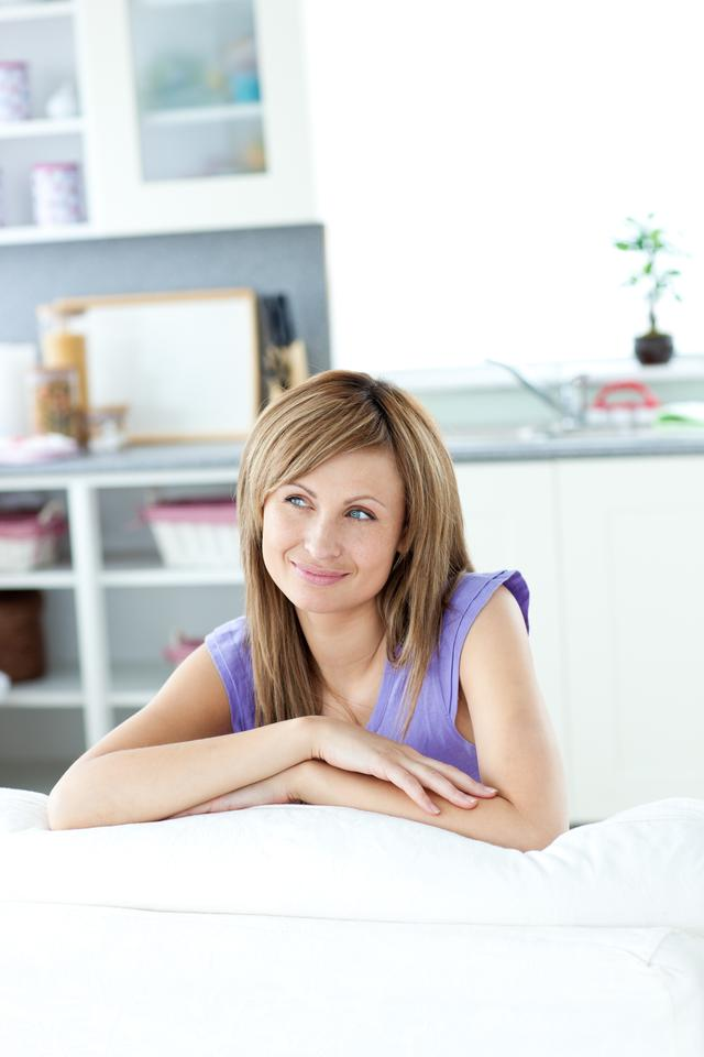 """""""Captivating woman sitting on a sofa looking to the side"""" stock image"""