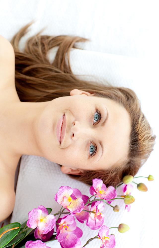 """""""Captivating young woman lying on a massage table with flowers"""" stock image"""