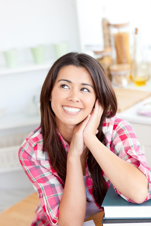 """""""Captivating woman sitting in the kitchen with her books"""" stock image"""