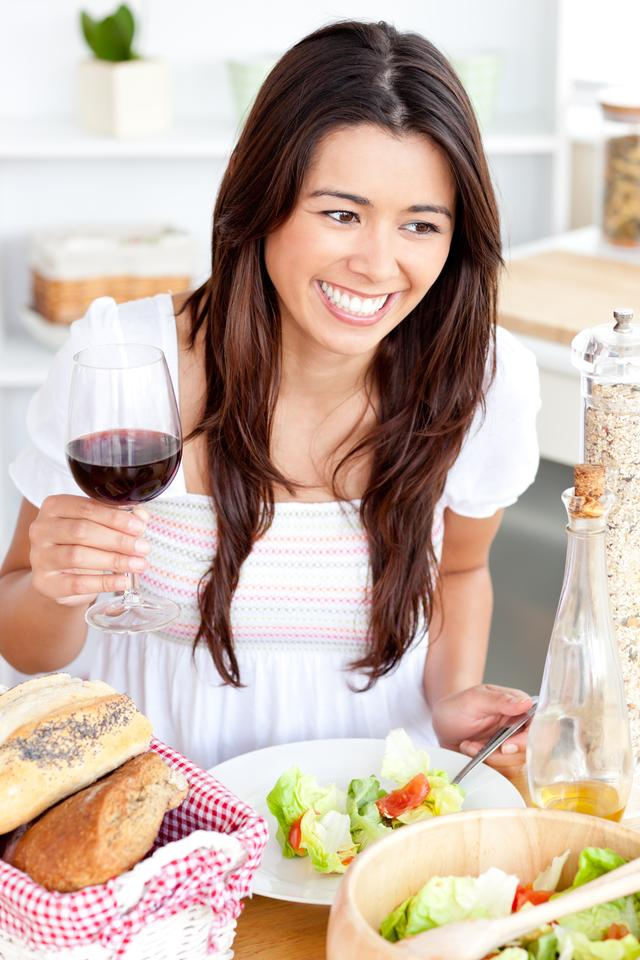 """""""Captivating woman holding a wineglass eating a salad at home"""" stock image"""