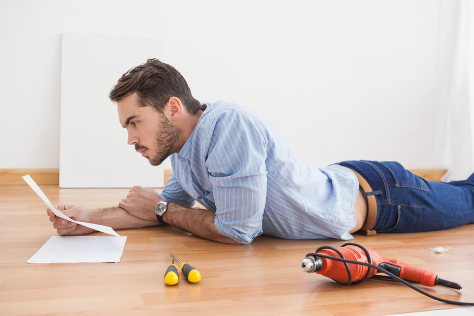 """""""Casual man reading instruction manual for power tool"""" stock image"""