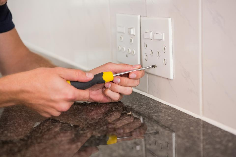 """""""Electrician unscrewing face plate of plug socket"""" stock image"""