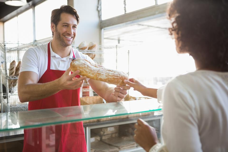 """Smiling baker doing loaf transaction with customer"" stock image"
