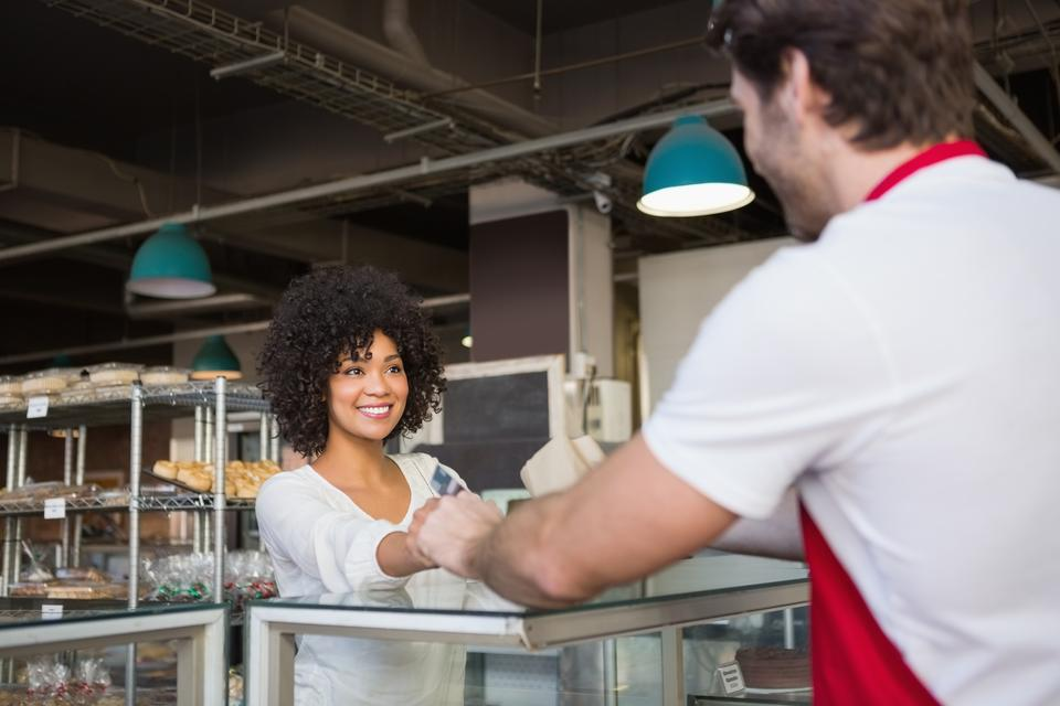 """Smiling waiter doing transaction with customer"" stock image"