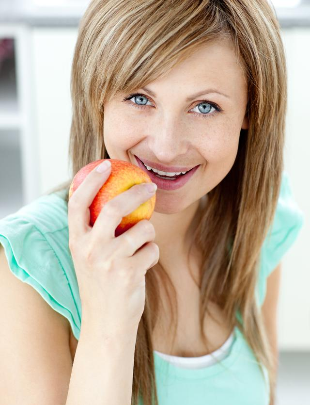 """""""Captivating woman eating an apple in the kitchen"""" stock image"""
