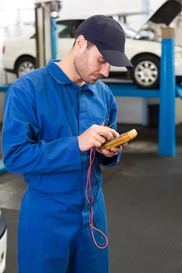 """Mechanic using a diagnostic tool"" stock image"