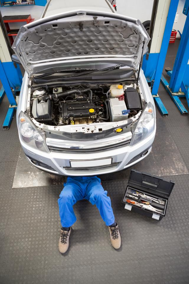 """""""Mechanic lying and working under car"""" stock image"""