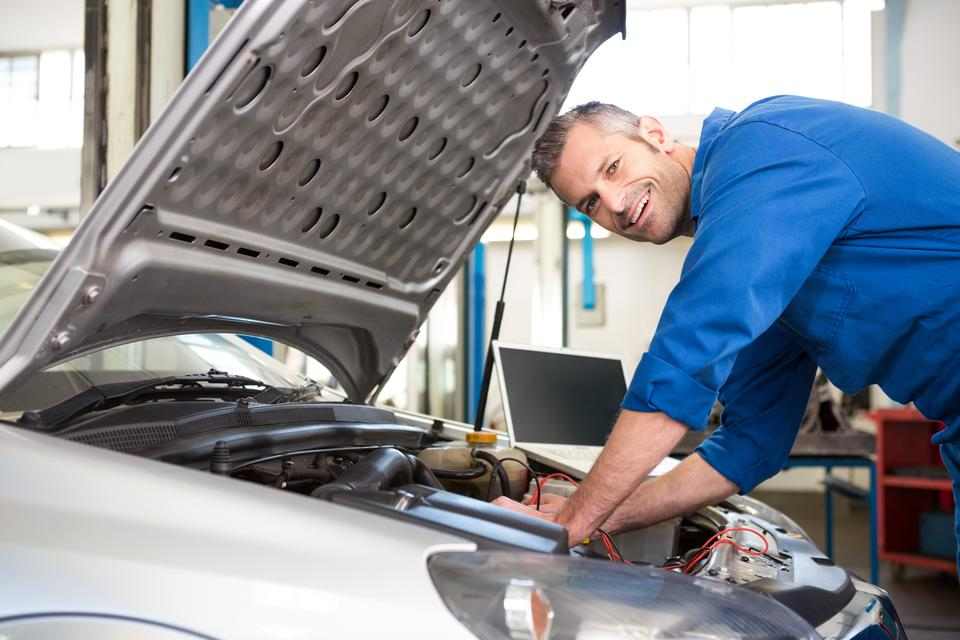 """Mechanic using diagnostic tool on engine"" stock image"