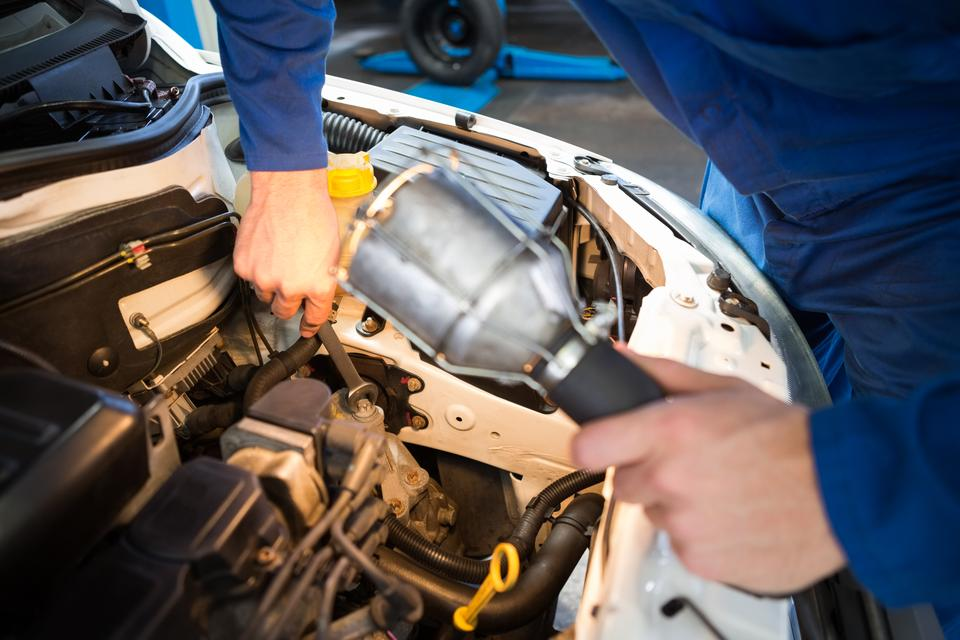"""""""Mechanic examining under hood of car with torch"""" stock image"""