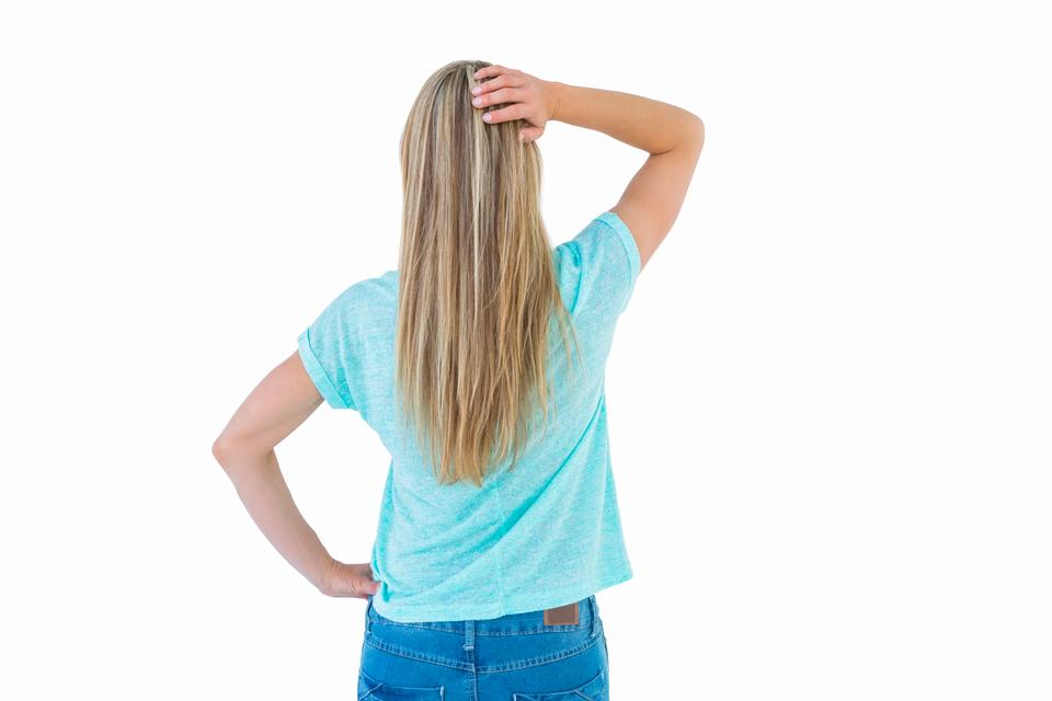 """Rear view of a blonde posing with hand on hip"" stock image"