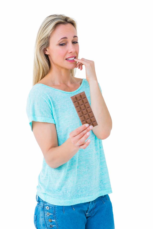 """""""Pretty blonde feeling guilty to eat bar of chocolate"""" stock image"""