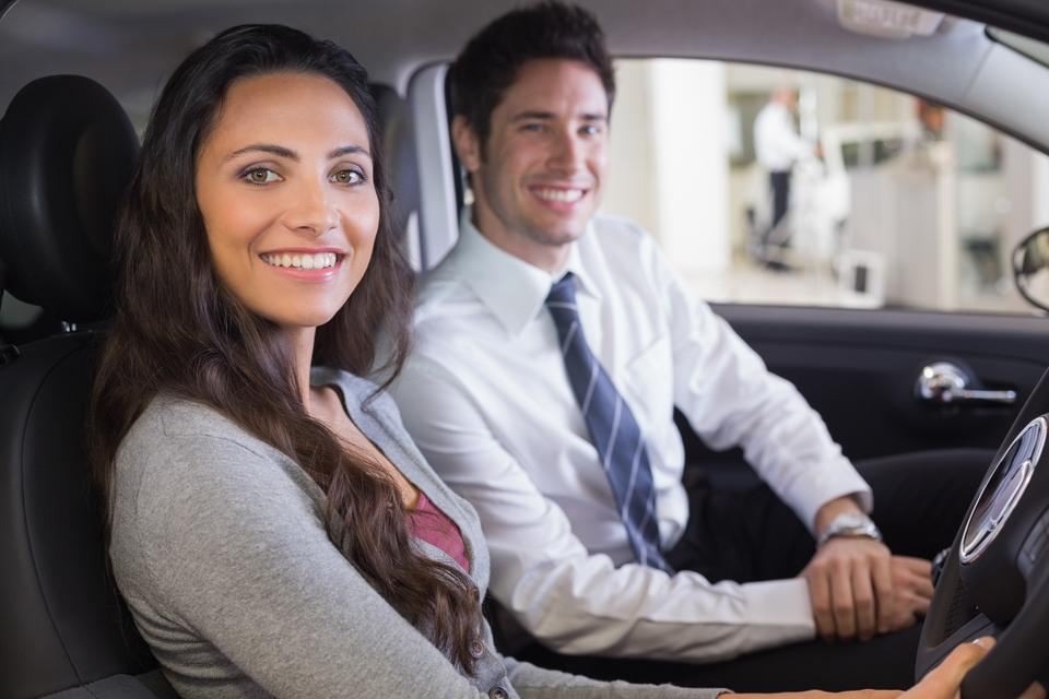 """""""Female driver at the wheel sitting in her car with salesperson"""" stock image"""