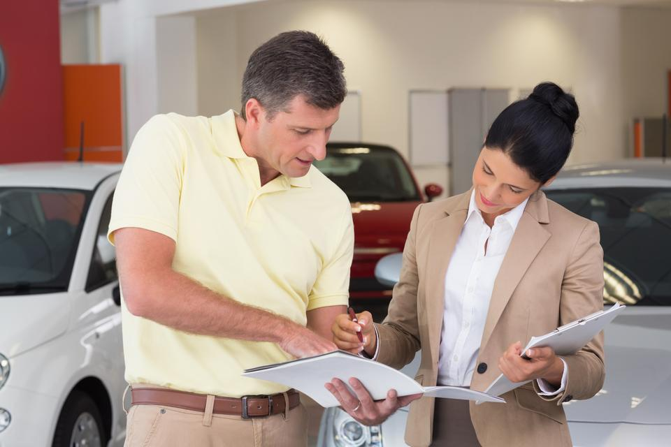 """""""Salesperson talking with her customer while holding a booket"""" stock image"""