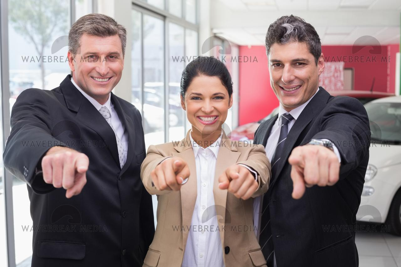 """Smiling business team pointing at camera"" stock image"