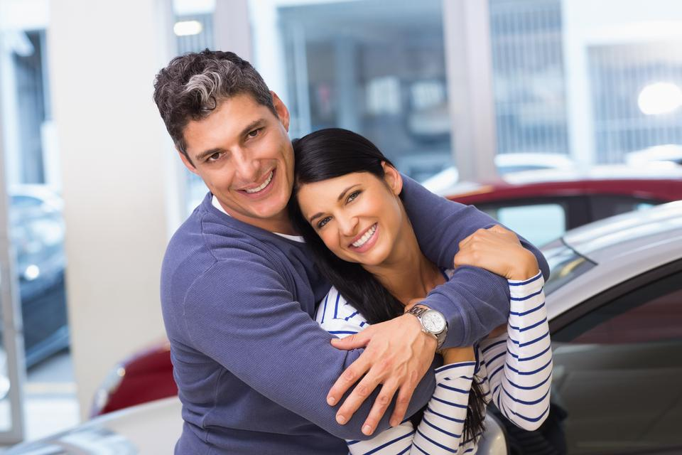 """Happy couple smiling at camera and embracing"" stock image"