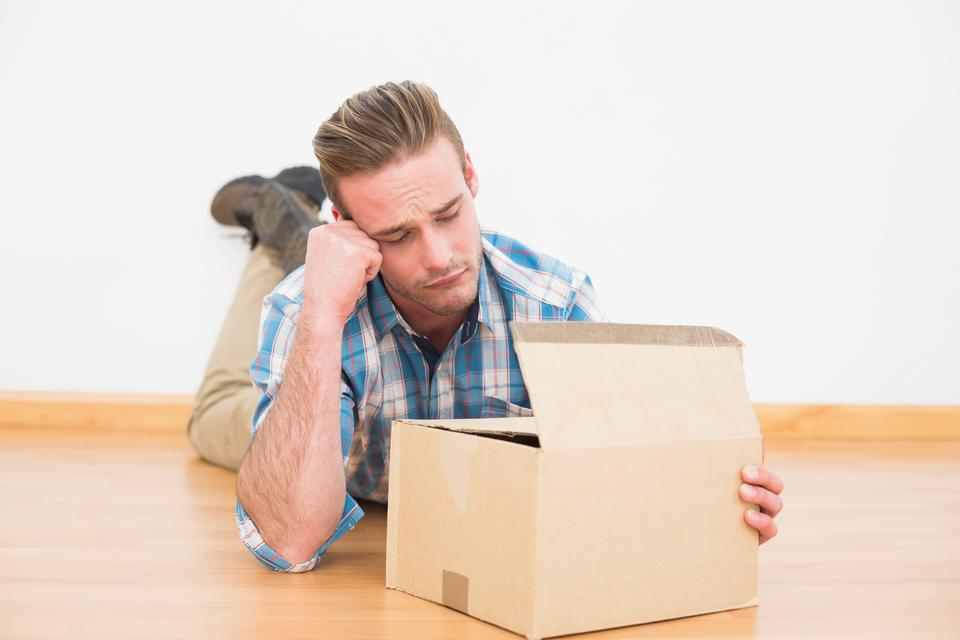 """""""Disappointed man lying on the floor opening gift"""" stock image"""