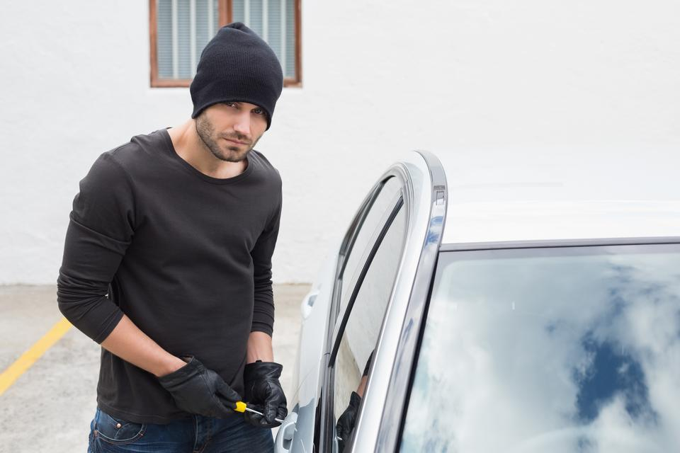 """""""Thief breaking into car with screwdriver"""" stock image"""