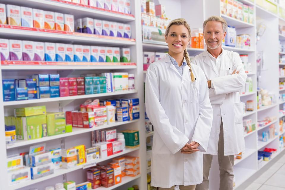 """Pharmacist with his trainee standing and smiling at camera"" stock image"
