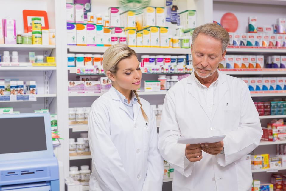 """Pharmacist and trainee talking together about prescription"" stock image"