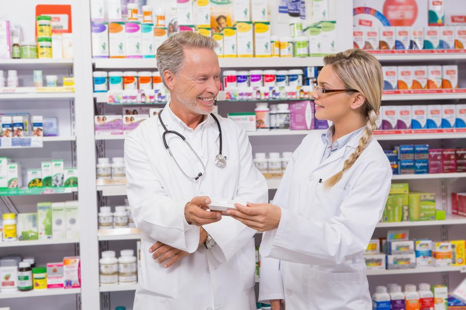 """Pharmacist speaking with his trainee about medicine"" stock image"