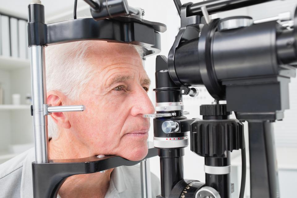 """""""Man looking into slit lamp"""" stock image"""