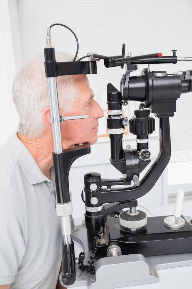 """""""Senior patient looking into slit lamp"""" stock image"""
