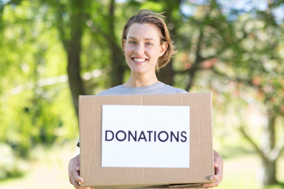 """""""Happy volunteer in the park holding box"""" stock image"""