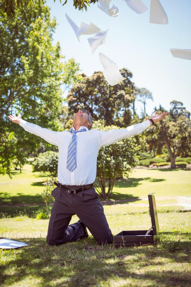 """Businessman tossing papers in the park"" stock image"