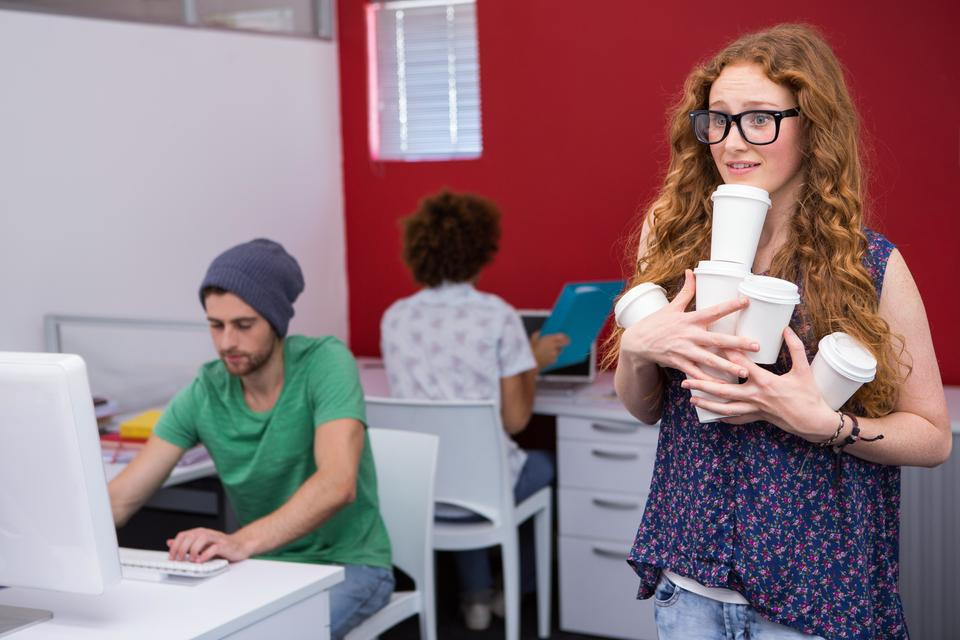 """""""Casual businesswoman carrying disposables glasses in office"""" stock image"""