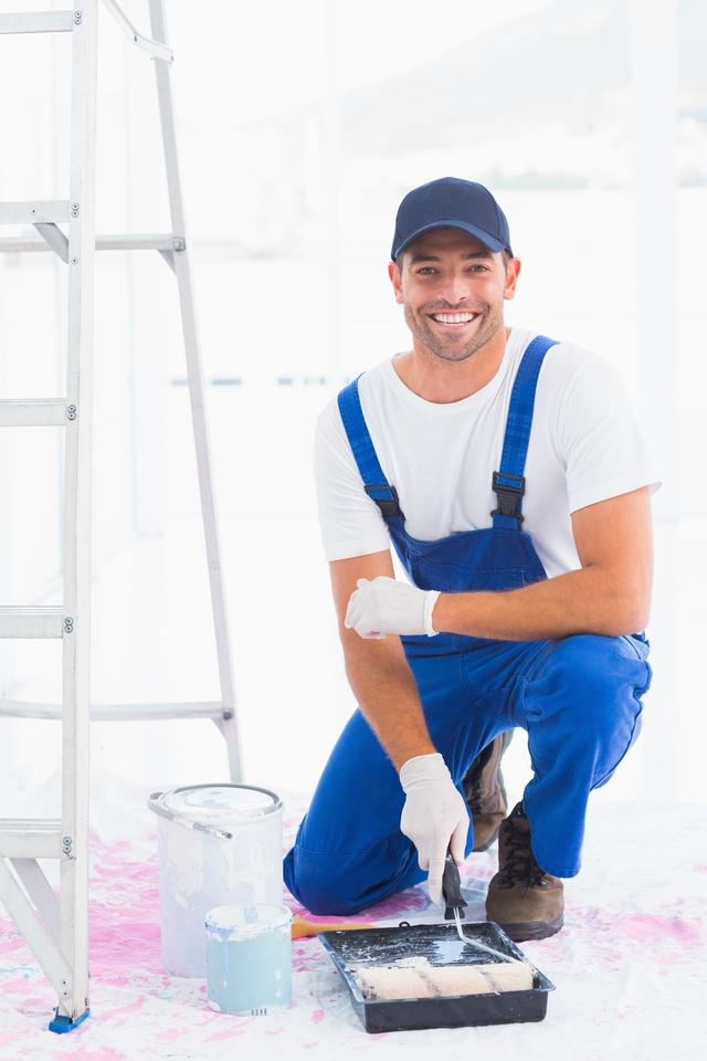 """""""Portrait of smiling handyman using paint roller in tray"""" stock image"""