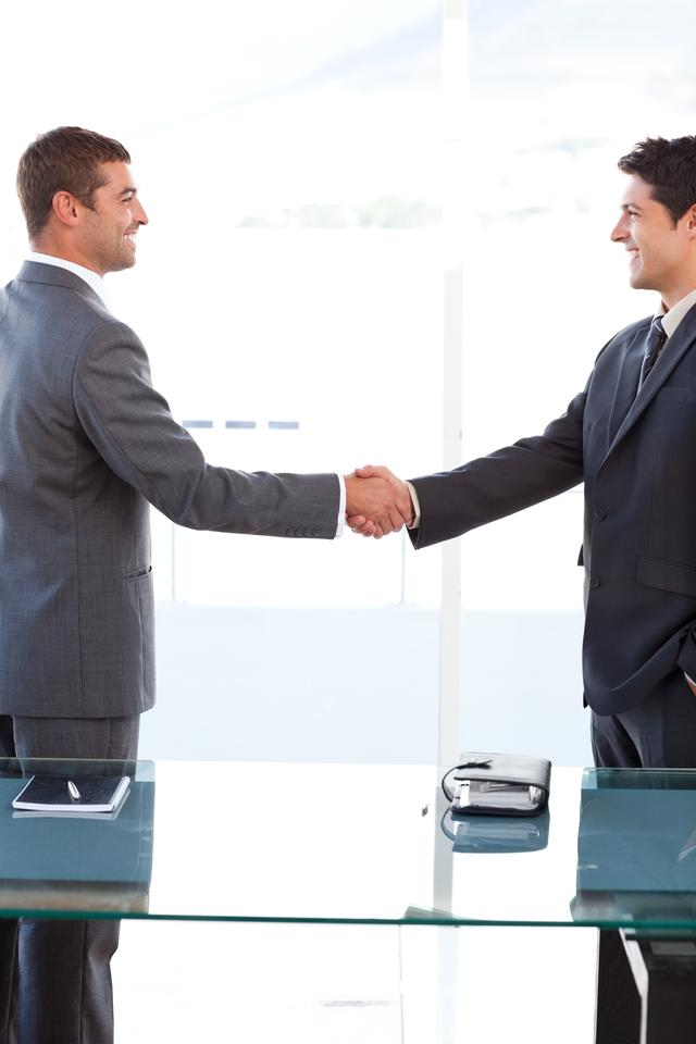 """""""Cheerful businessmen closing a deal by shaking their hands"""" stock image"""