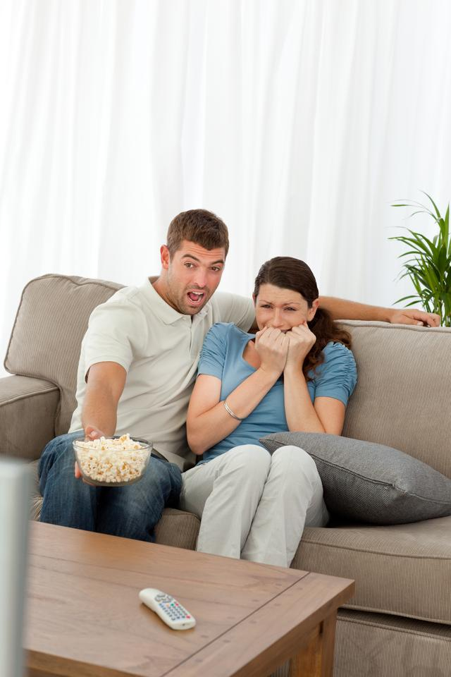 """""""Terrified couple watching a horror movie in the living room"""" stock image"""