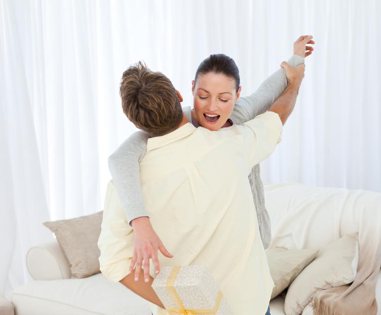 """""""Excited woman catching a present hidden behind her boyfriend"""" stock image"""