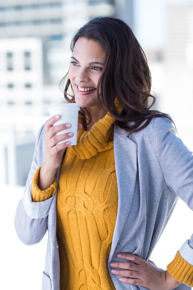 """Beautiful woman drinking a coffee with hand on hip"" stock image"