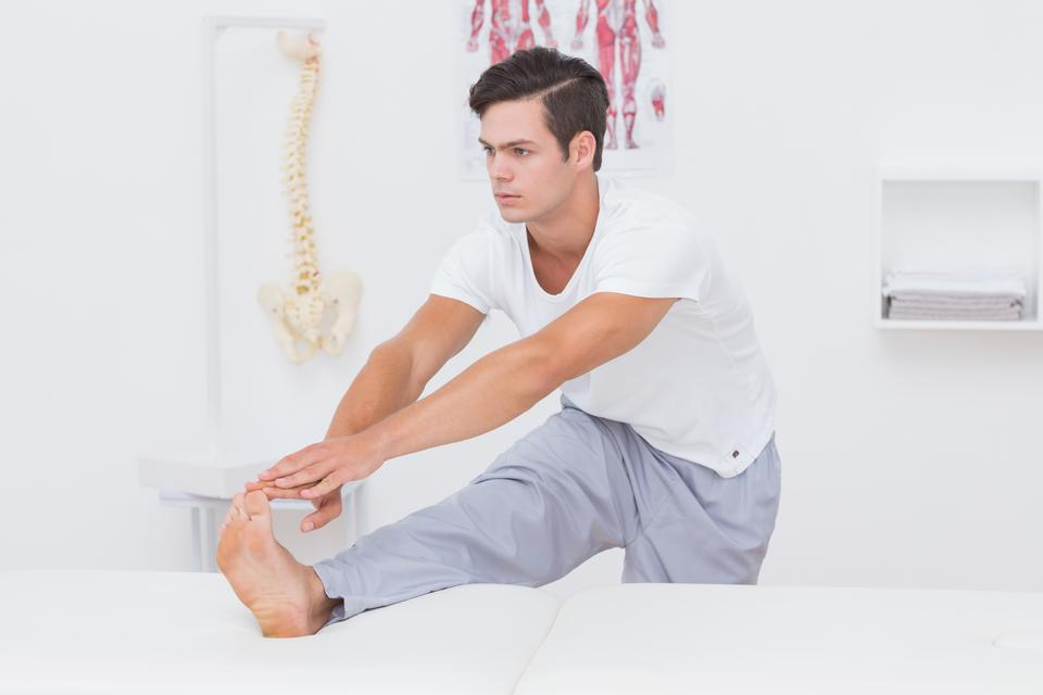 """Patient stretching his leg on bed"" stock image"