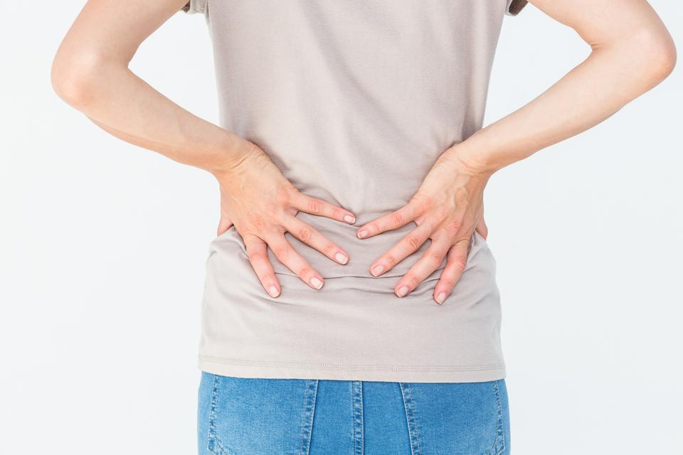 """""""Woman having a back ache and holding her back"""" stock image"""