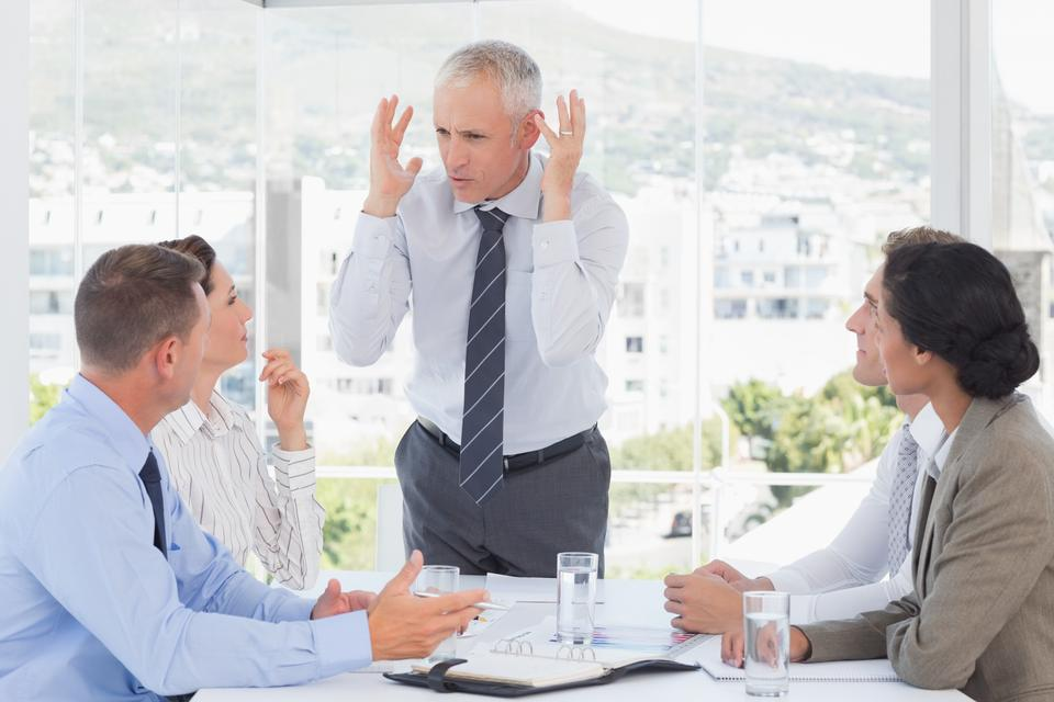"""Irritated businessman talking to his team"" stock image"