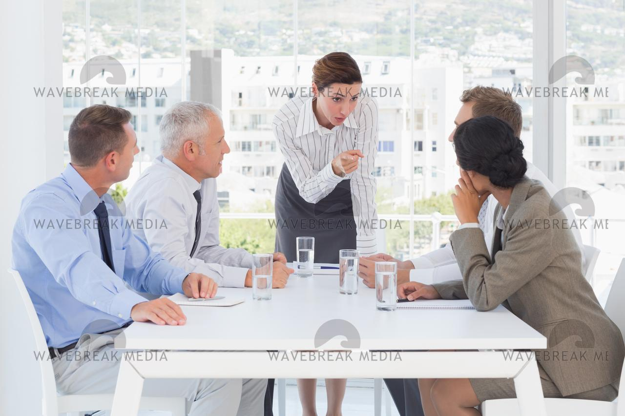 """Irritated businesswoman talking to her colleague"" stock image"