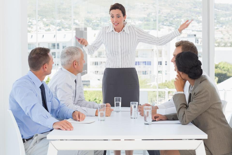 """Irritated businesswoman talking to her colleagues"" stock image"
