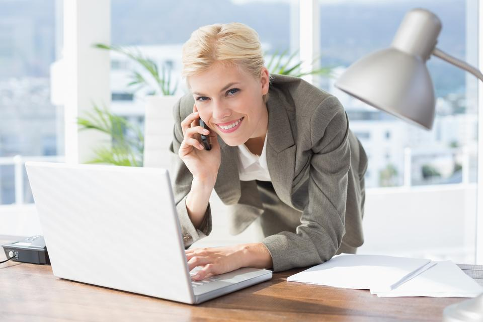 """""""Smiling businesswoman on the phone looking at camera"""" stock image"""