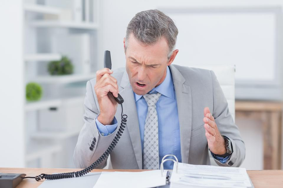 """Irritated businessman answering phone"" stock image"