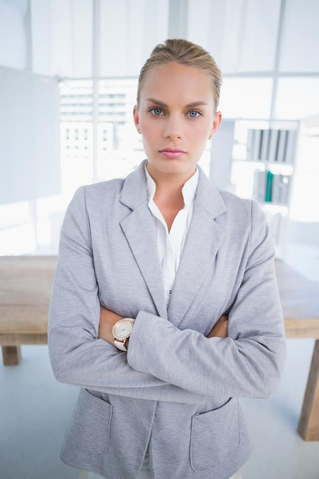 """Unhappy businesswoman looking at camera with arms crossed"" stock image"