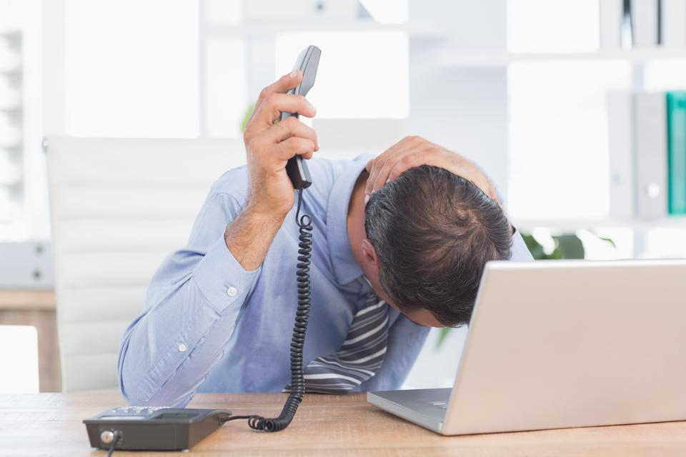 """""""Frustrated businessman phoning at his desk"""" stock image"""