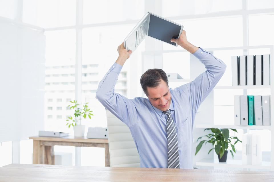 """Irritated businessman trying to broke his laptop"" stock image"